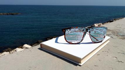 mare riflesso negli occhiali da sole sul libro