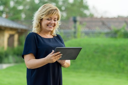 Outdoor portrait of mature business woman with digital tablet, background green garden of a private residence