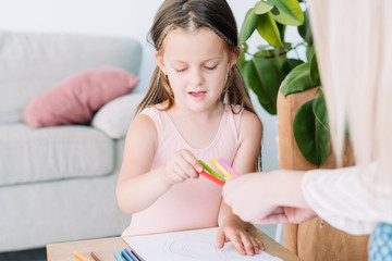 child drawing hobby. artful kids leisure. little girl choosing a pencil to express her imagination on paper.