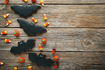Halloween gingerbread cookies with candies on grey wooden table