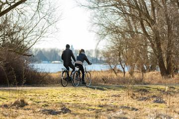 """Couple biking in park  """"de Oeverlanden"""" aan de Nieuwe Meer in Amsterdam, the Netherlands."""