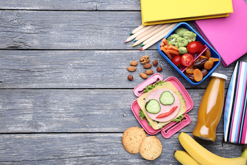 School lunch box with vegetables and bottle of juice on wooden table