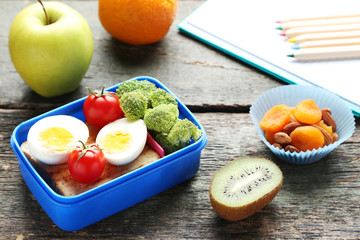Foto op Canvas Assortiment School lunch box with sandwich and eggs on wooden table
