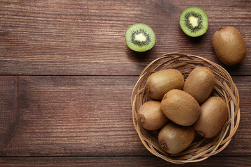 Kiwi fruits in basket on brown wooden table
