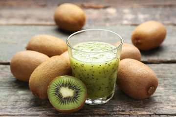 Wall Mural - Fresh kiwi smoothie in glass on grey wooden table