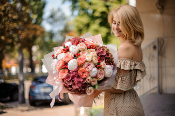 Smiling beautiful girl holding a bouquet of passionate flowers