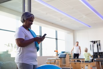 Senior women using mobile phone in gym