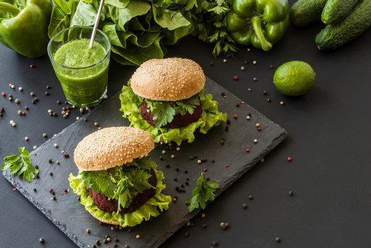 Vegan burgers with beet cutlet and green smoothies on black background. Healthy vegan food. Detox diet.
