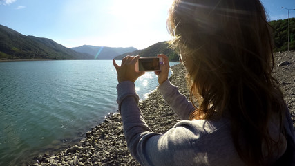 Female filming mountain landscape and river on smartphone, sunny day beauty