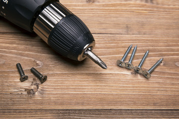 screwdriver and screws on a wooden table