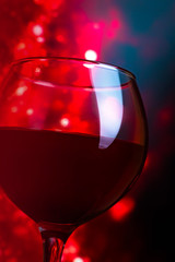 Glass with red wine on a dark red background