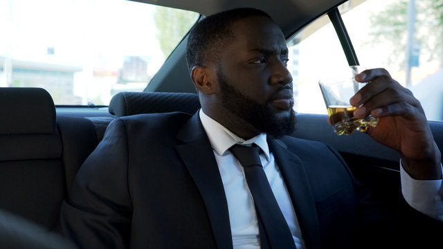 Thoughtful African American man sitting on back seat of car with alcohol drink