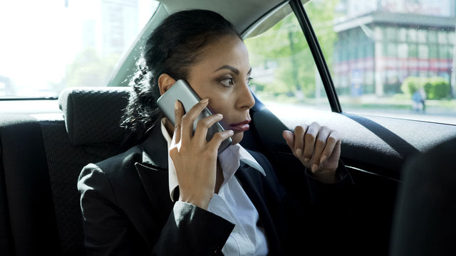 Attractive businesswoman sitting in taxi, talking on phone, serious conversation