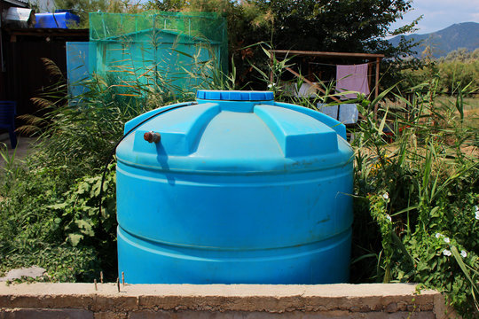blue large plastic water tank near house in an arid region. Settlement in the territory of the Republic of Crimea