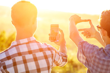 two men take pictures of the sunset on the phone in the sun