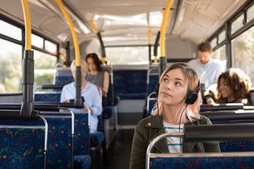 Woman listening music while travelling in modern bus