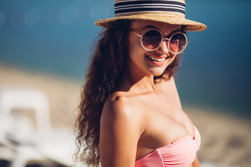 Cool hipster girl in summer straw hat posing beside exotic summer beach hot summer fashion accessory,stylish sunglasses,bikini.Sexy perfect fit body woman. Copy, empty space for text