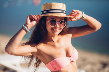 Close-up portrait of cheerful curly dark hair woman in sunglasses touching her hat on blur background. posing beside exotic summer beach hot summer