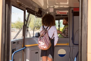 Female commuter taking ticket from driver in modern bus