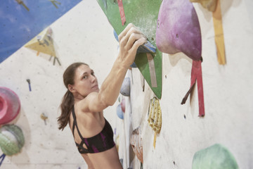 Woman with perfect fit body training on a climbing wall in sport hall, doing exercise, workout.