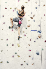 Woman with perfect fit body training on a climbing wall in sport hall, doing exercise, workout