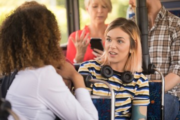 Female friends interacting while travelling in modern bus