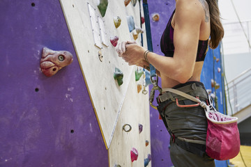 Woman with perfect fit body training on a climbing wall in sport hall, ready to workout