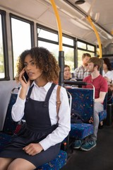 Female commuter talking on mobile phone while travelling in