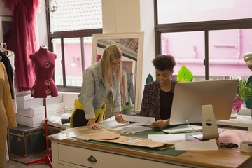 Fashion designer discussing at desk