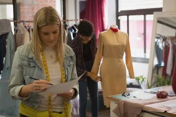 Fashion designer checking sketch in fashion studio
