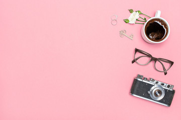 Flay lay, Top view office table desk. Feminine desk workspace frame with cup of coffee, glasses, camera, rings and a rose branch on a pink back ground with space for text
