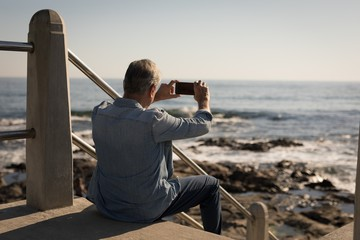 Senior man taking pictures from mobile phone