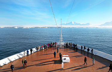 Tourist on Cruise Ship Deck Heading to Anarctic Peninsula, Ice covered Land Ahead
