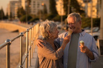Senior couple having ice cream at promenade