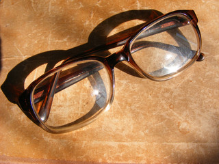 Reading glasses and old book, glasses on aged shabby background