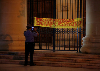A police officer takes a photo while awaiting instructions on whether to remove a protest banner hanging on the entrance to the Courts of Justice in Malta