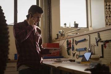Mechanic talking on mobile phone in workshop