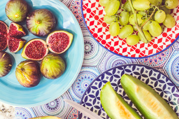 Healthy, fruit breakfast - figs, melon and grapes on colorful plates; summer fruit