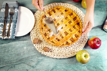 Top view, home made apple pie, woman preparing to serve. Beautiful marble table background