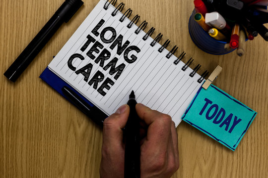 Writing note showing Long Term Care. Business photo showcasing Adult medical nursing Healthcare Elderly Retirement housing Man holding marker notebook clothespin reminder wooden table markers.
