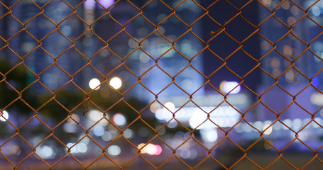 Woven wire fence with blur city view at night