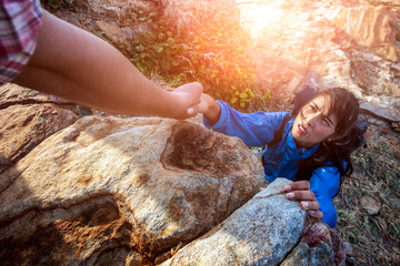 A male climber pulls a couple of hands up from below. Ideas for success, teamwork, and leadership.
