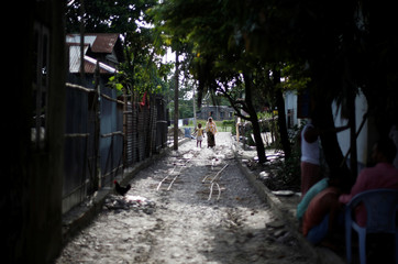 A woman and her daughter walk along a road in Dhubri district