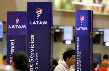 Passengers walk near the LATAM airlines counter at Jorge Chavez airport in Callao