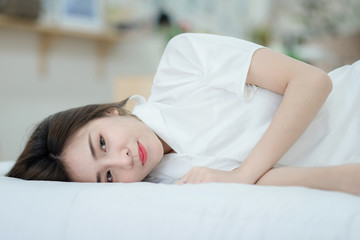 A beautiful young woman lying in bed comfortably and happily. Happy morning. Portrait of a smiling pretty young  woman relaxing in white bed.