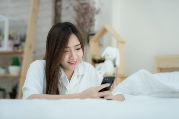 Beautiful Asian woman use of the smartphone sitting beside the bed.
