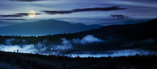 panorama of countryside at night in full moon light. beautiful landscape in mountains with fog rising above the valley and hill