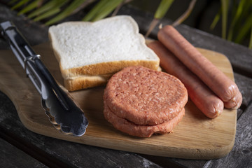 Fresh uncooked barbecue sausages, burgers and bread