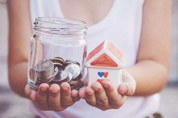 Small kid hands holding house and coins