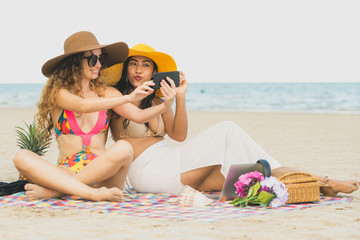 Happy women taking photo on sand beach in summer.